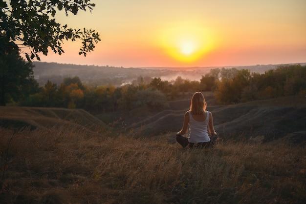Fille méditant au coucher du soleil