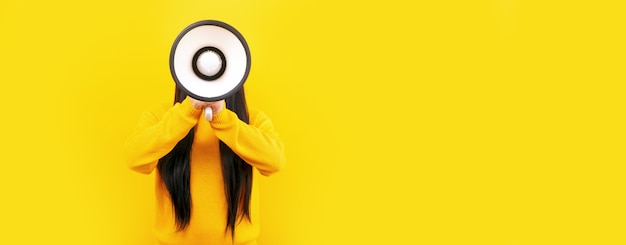 Fille avec un mégaphone sur un espace jaune