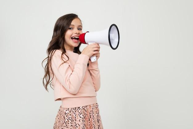 Fille avec un mégaphone en main sur le côté sur un mur de studio blanc avec espace vide