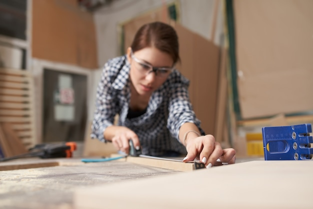 Fille menuisier avec planche de bois derrière l'établi en atelier