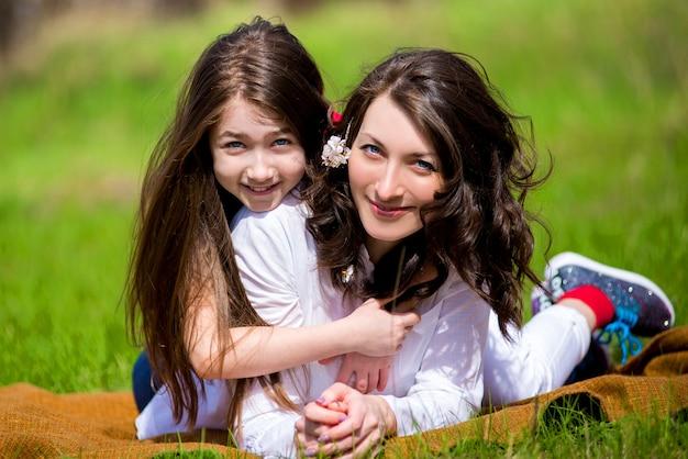 Fille avec la mère assise sur l'herbe au printemps et communiquer