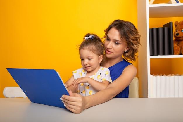 Fille avec mère assise à la table ensemble et faire ses devoirs