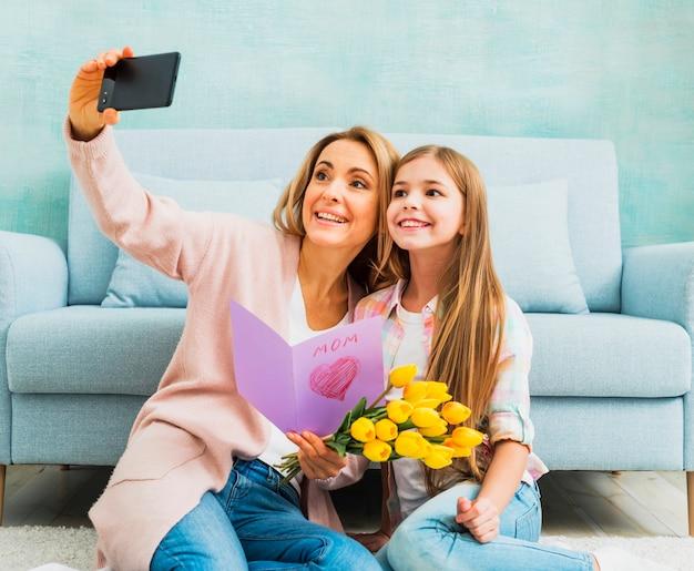 Fille et mère avec des cadeaux prenant selfie