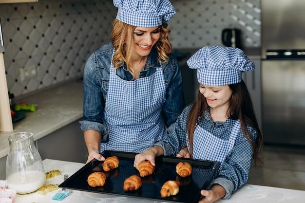 Fille et mère des croissants au four. concept de famille
