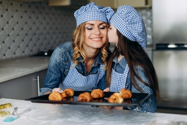 Fille et mère des croissants au four. fille embrassant sa mère heureuse. concept de famille