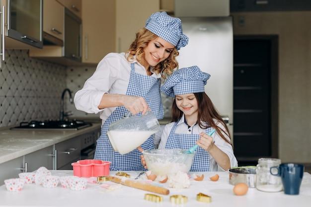 Fille et mère cuisinent. mère verse du lait et une fille souriante. concept de famille