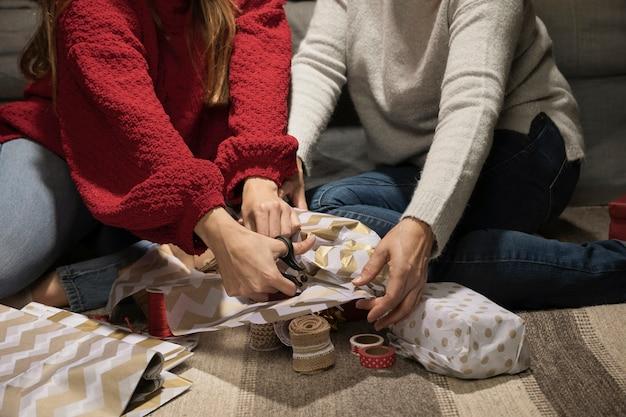 Fille et mère emballant des cadeaux