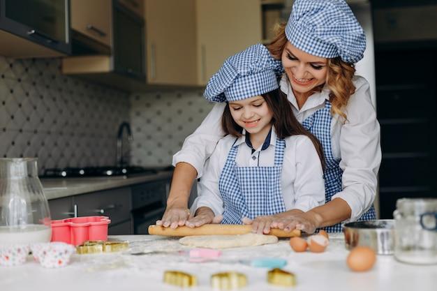 La fille et la mère étalent la pâte avec un rouleau à pâtisserie. concept de famille