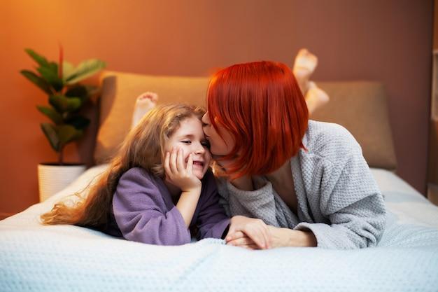 Fille et mère jouant sur le lit dans la pépinière