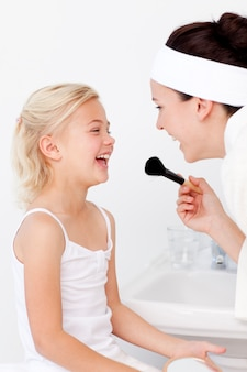 Fille et mère jouant avec le maquillage