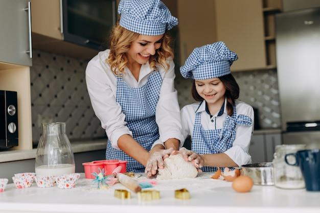 Fille et mère remuent la pâte dans la cuisine.