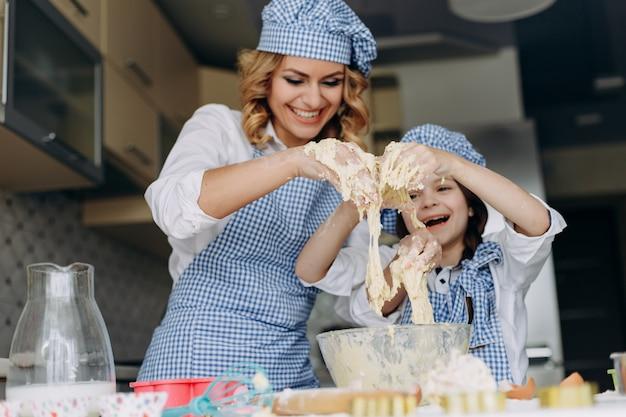 La fille et la mère remuent la pâte et s'amusent bien. concept de famille