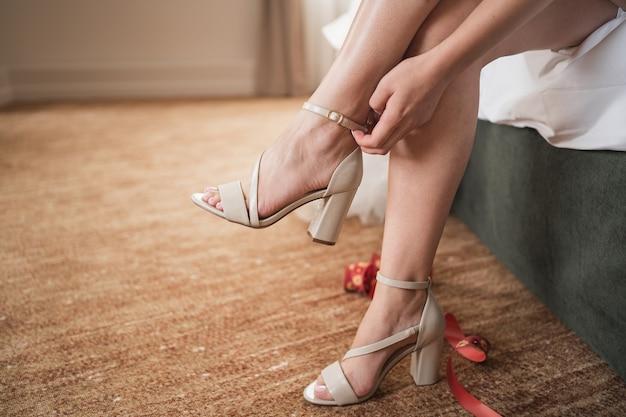 La fille met des chaussures la mariée va au marié la fille attache ses sandales gros plan de chaussures...
