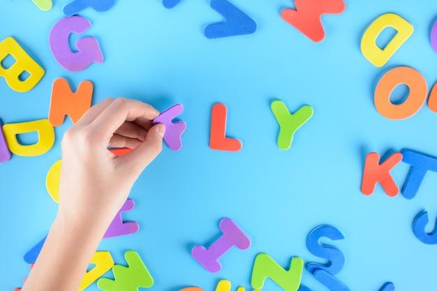 La fille met hors des lettres multicolores les mots volent. beau fond.