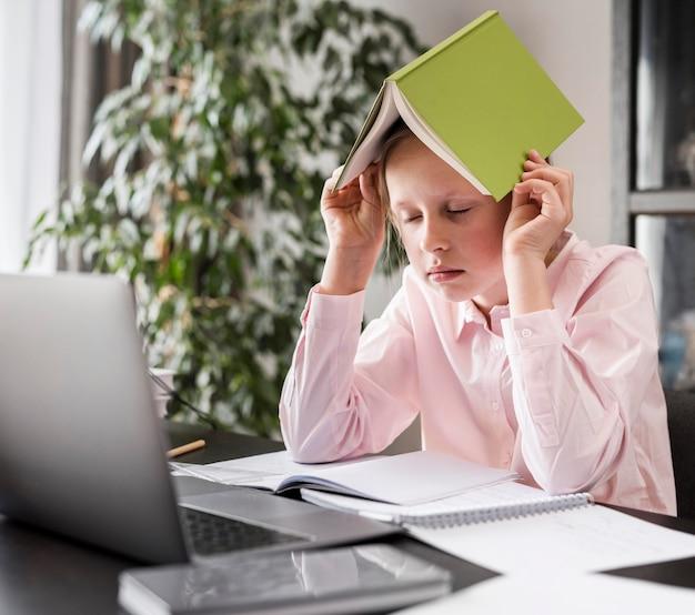 Fille mettant un livre sur sa tête