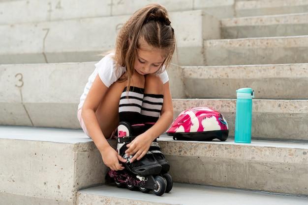 Fille mettant des patins à roues alignées