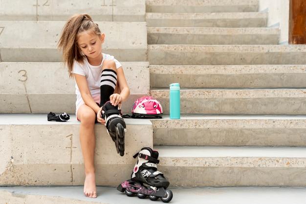 Fille mettant des patins à roulettes noirs