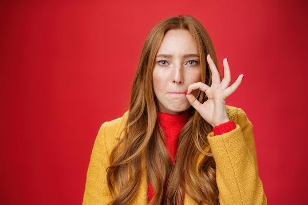 Fille mettant le sceau sur la bouche en promettant de ne dire aucun secret à personne, suçant les lèvres et tenant le doigt près de la fermeture éclair pour ne pas répandre des mots, l'air sérieux et déterminé à garder la surprise en sécurité sur le mur rouge.