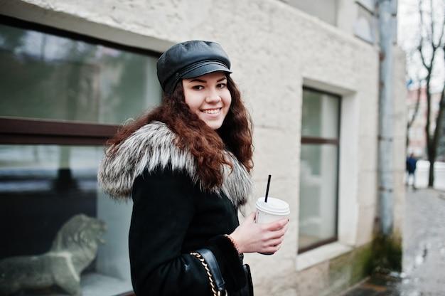Fille mexicaine bouclée en capuchon en cuir et une tasse en plastique de café à la main à pied dans les rues de la ville.