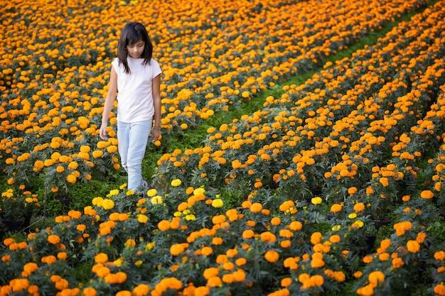 Fille mexicaine marchant dans un champ de fleurs de cempasuchil à xochimilco