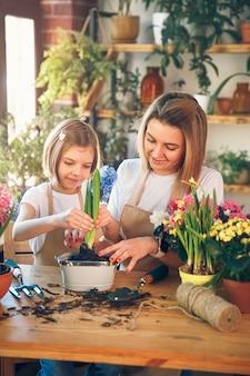 Une fille mignonne aide sa mère à prendre soin des plantes. maman et sa fille se livrent au jardinage. héhé au printemps.