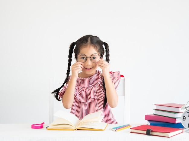 Fille mignonne asiatique avec un livre sur le bureau