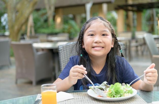 Fille mignonne asiatique profiter de manger une salade de légumes