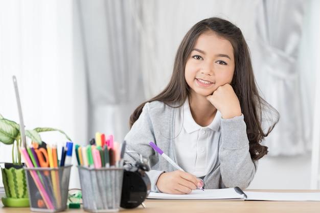 Fille mignonne asie écrit quelque chose dans le papier avec des crayons de couleur