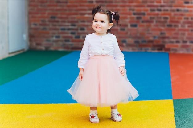 Fille mignonne de bambin en costume de ballerine au beau jardin d'été.