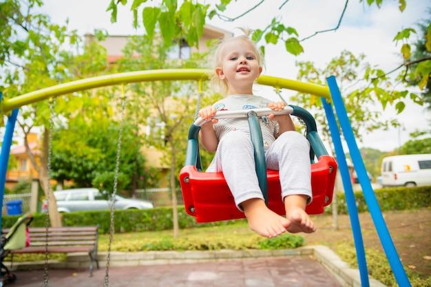 Fille mignonne blanche à cheval sur une balançoire sur le terrain de jeu en été.