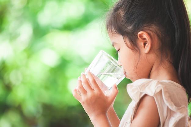 Fille mignonne enfant asiatique boire de l'eau douce du verre