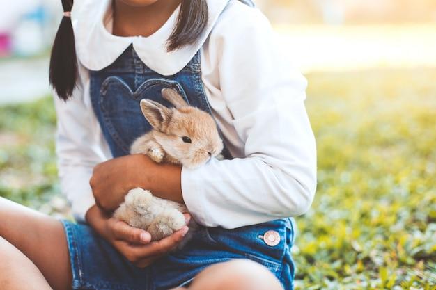 Fille mignonne enfant asiatique jouant avec petit lapin avec amour et tendresse