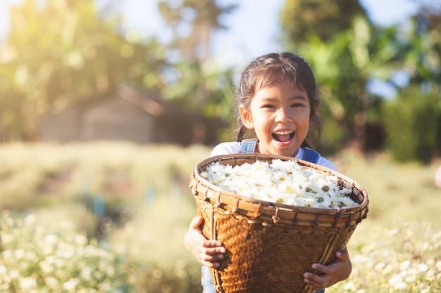 Fille mignonne enfant asiatique portant le panier de belle fleur dans le champ de fleurs avec bonheur