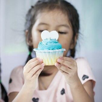Fille mignonne enfant asiatique tenant délicieux cupcake bleu