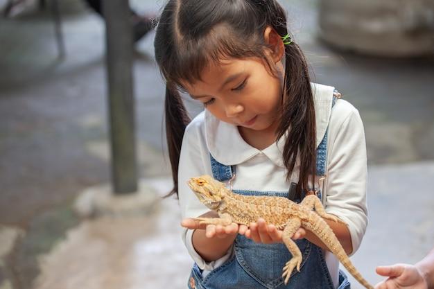 Fille mignonne enfant asiatique tenant et jouant avec caméléon avec curieux et amusant