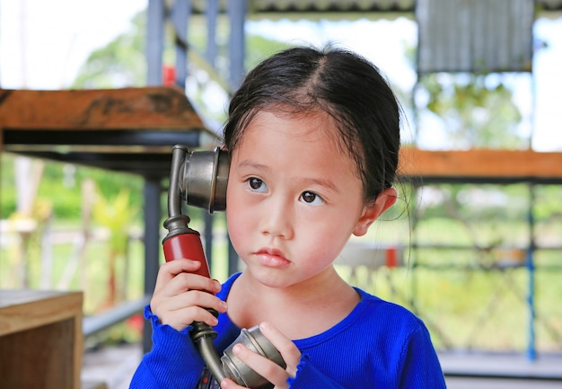 Fille mignonne enfant asiatique en utilisant le téléphone rétro.