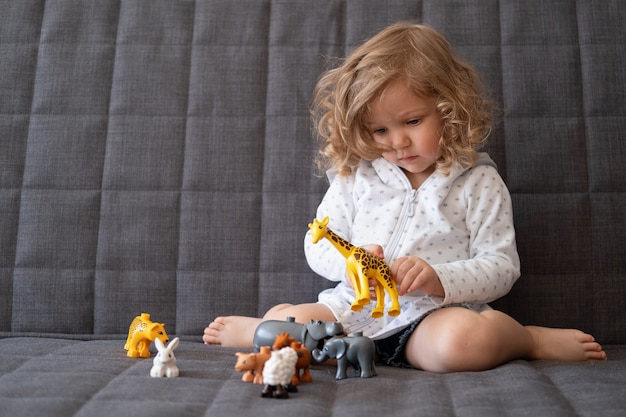 Fille mignonne enfant en bas âge bouclé jouant avec avec zoo jouet assis sur le canapé. jouets pour petits enfants. développement précoce