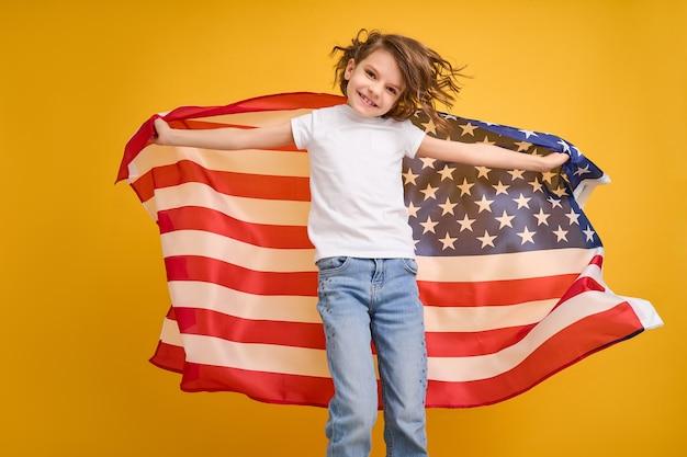 Fille mignonne d'enfant heureux avec le drapeau américain sur le jaune