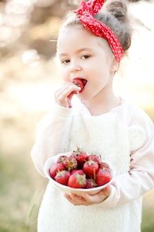 Fille mignonne d'enfant mangeant des fraises fraîches dehors