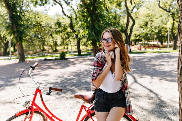 Fille mignonne galbée posant avec vélo dans le parc. heureuse dame européenne, passer la matinée d'été en plein air.