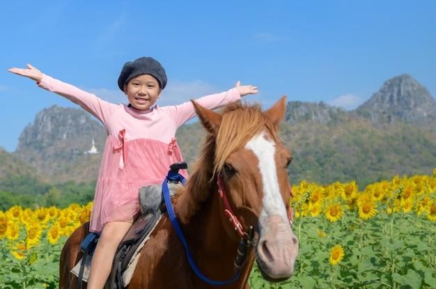 Fille mignonne heureuse cheval dans le champ de tournesols