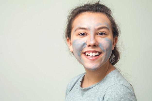 Fille mignonne et heureuse frotte le visage avec de l'argile cosmétique et des sourires