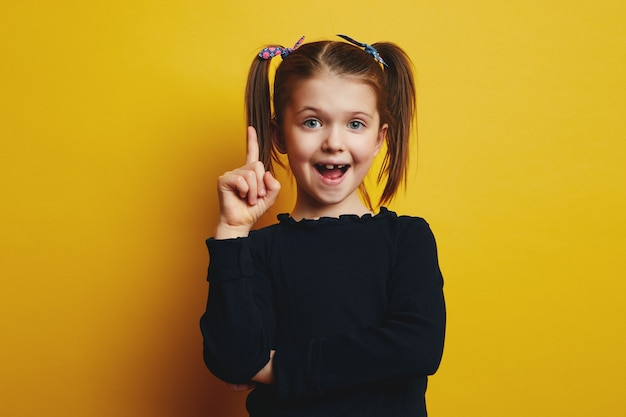 Fille mignonne intelligente ouvrant la bouche et pointant vers le haut tout en ayant une bonne idée