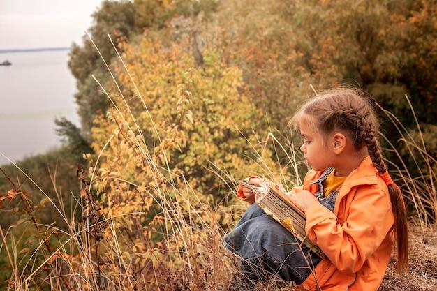 Fille mignonne intelligente tenant un livre avec des feuilles jaunes sèches