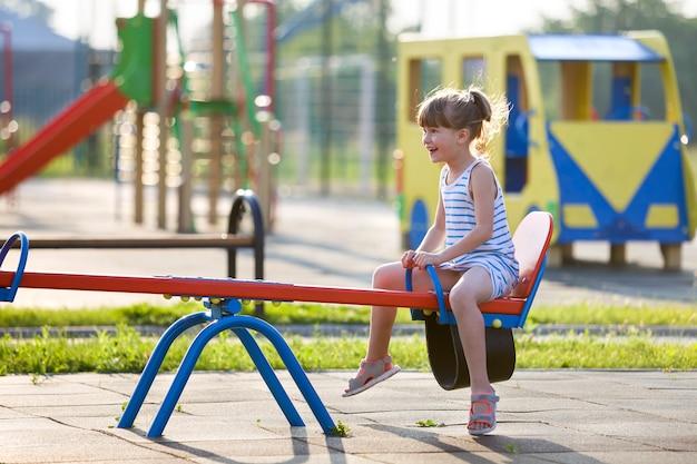 Fille mignonne jeune enfant à l'extérieur sur balançoire en balançoire journée d'été ensoleillée.