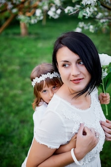 Fille mignonne et mère étreignant dans le jardin de printemps en fleurs femme heureuse et enfant, vêtue d'une robe blanche à l'extérieur, la saison du printemps arrive. concept de vacances fête des mères