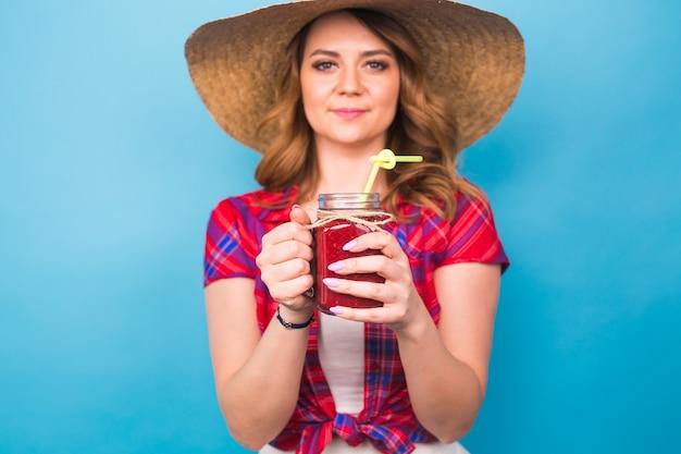 Fille mignonne sexy posant en studio, buvant du jus de fruit ou un cocktail sur fond bleu et espace de copie