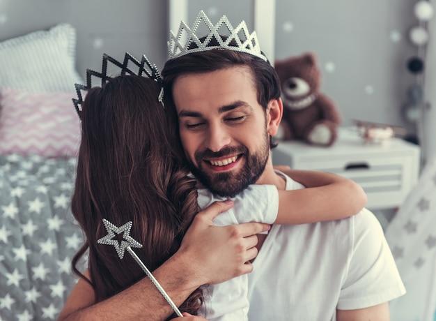 Une fille mignonne et son beau papa en couronne s'enlacent.