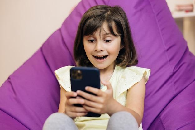 Une fille mignonne tient un enfant de téléphone à l'aide d'un enfant de smartphone naviguant sur internet