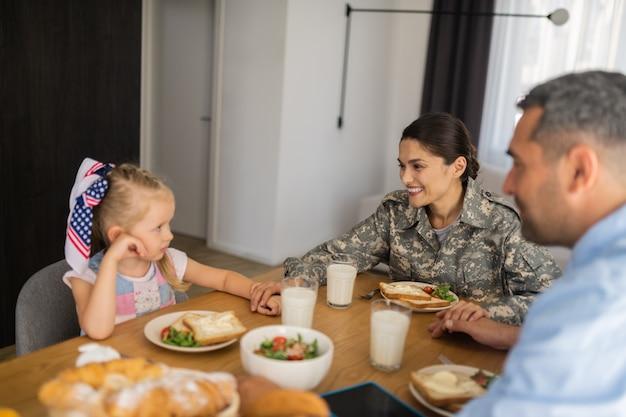 Fille mignonne touchante. femme soldat aux cheveux noirs touchant sa jolie fille tout en prenant son petit-déjeuner en famille
